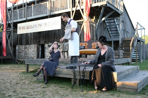Marie auditions for Old Marthy in Anna Christie. Claire Dubrey (Allie Dunbar) standing in for Greta Garbo is served a drink by a barkeep (Jeff Schissler)